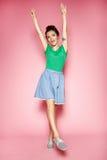 Retrato de la muchacha rizada hermosa que presenta en el fondo rosado Fotografía de archivo