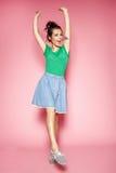 Retrato de la muchacha rizada hermosa que presenta en el fondo rosado Imagenes de archivo