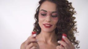 Retrato de la muchacha rizada joven divertida sonriente que mira dos halfs de las pimientas de chile candentes Movimientos del fo metrajes