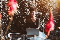 Retrato de la muchacha rizada negra en parque con el ordenador portátil Imágenes de archivo libres de regalías