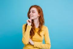 Retrato de la muchacha roja del pelo del jengibre feliz con las pecas que sonríe mirando la cámara Fondo azul en colores pastel C Foto de archivo