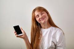 Retrato de la muchacha rojo-dirigida joven con las pecas que sostienen el teléfono Imagen de archivo libre de regalías