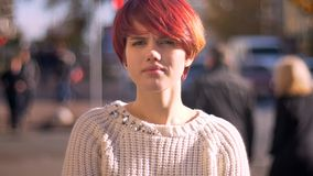 Retrato de la muchacha rosado-cabelluda caucásica joven que mira en cámara tranquilamente en fondo soleado de la ciudad fotos de archivo