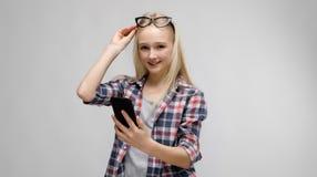 Retrato de la muchacha rubia adorable dulce sonriente atractiva del adolescente en ropa a cuadros con los vidrios en su tenencia  Foto de archivo