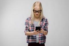 Retrato de la muchacha rubia adorable dulce sonriente atractiva del adolescente en ropa a cuadros en los vidrios que sostienen el Imágenes de archivo libres de regalías