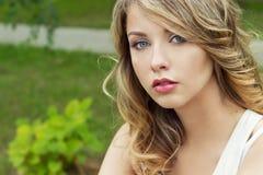 Retrato de la muchacha rubia atractiva hermosa en un parque con los labios regordetes grandes Foto de archivo libre de regalías