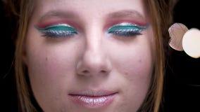 Retrato de la muchacha rubia caucásica con maquillaje colorido brillante que mira pacífico en cámara en luces borrosas almacen de video