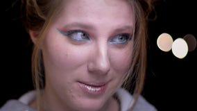 Retrato de la muchacha rubia con el maquillaje colorido que intenta soplar su pelo de la cara en fondo borroso de las luces almacen de video