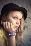 Retrato de la muchacha rubia hermosa en pulsera del telar del sombrero y del caucho Fotografía de archivo libre de regalías