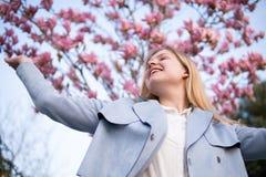 Retrato de la muchacha rubia hermosa que presenta con las ramas de ?rbol florecientes de la magnolia con las flores rosadas en fo foto de archivo libre de regalías