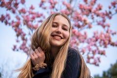 Retrato de la muchacha rubia hermosa que presenta con las ramas de ?rbol florecientes de la magnolia con las flores rosadas en fo imágenes de archivo libres de regalías