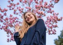 Retrato de la muchacha rubia hermosa que presenta con las ramas de ?rbol florecientes de la magnolia con las flores rosadas en fo imagenes de archivo