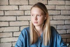 Retrato de la muchacha rubia joven con los auriculares Imagen de archivo libre de regalías