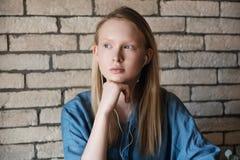 Retrato de la muchacha rubia joven con los auriculares Restos principales de la muchacha en su mano Imagenes de archivo
