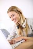Retrato de la muchacha rubia joven hermosa que trabaja en el ordenador portátil Imagen de archivo