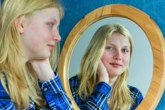 Retrato de la muchacha rubia que mira en espejo Foto de archivo libre de regalías