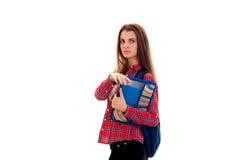 Retrato de la muchacha seria joven del estudiante con la mochila y de las carpetas para los cuadernos aislados en el fondo blanco Imagenes de archivo