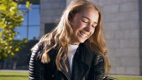 Retrato de la muchacha sonre?da bonita que manda un SMS en el smartphone usando el app en aire libre Forma de vida, urbana almacen de metraje de vídeo
