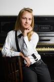 Retrato de la muchacha sonriente cerca de un piano interior Fotografía de archivo
