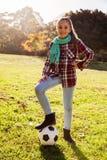 Retrato de la muchacha sonriente con el balón de fútbol en parque Fotografía de archivo