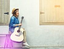 Retrato de la muchacha sonriente con la guitarra Foto de archivo libre de regalías