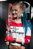 Retrato de la muchacha sonriente con un palo en el traje Harley Foto de archivo