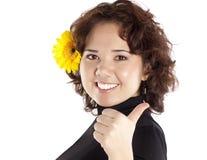 Retrato de la muchacha sonriente con una flor amarilla fotografía de archivo