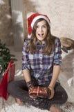 Retrato de la muchacha sonriente del adolescente en el sombrero de santa que lleva a cabo la Navidad Fotografía de archivo