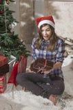 Retrato de la muchacha sonriente del adolescente en el sombrero de santa que lleva a cabo la Navidad Imágenes de archivo libres de regalías