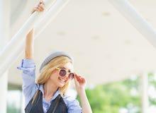 Retrato de la muchacha sonriente del inconformista en gafas de sol en la ciudad Imagenes de archivo