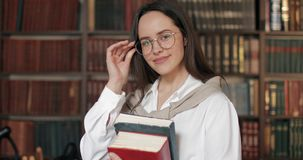 Retrato de la muchacha sonriente en biblioteca almacen de video