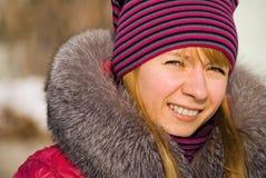 Retrato de la muchacha sonriente en casquillo hecho punto Imagen de archivo