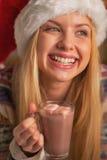 Retrato de la muchacha sonriente en el sombrero de santa con la taza de chocolate caliente Imagen de archivo libre de regalías