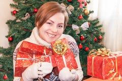 Retrato de la muchacha sonriente feliz atractiva que sostiene los regalos de la Navidad Fotos de archivo libres de regalías