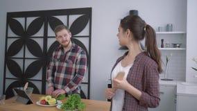 Retrato de la muchacha sonriente feliz en la cocina, miradas satisfechas de la mujer en el individuo que prepara la comida sana ú almacen de metraje de vídeo