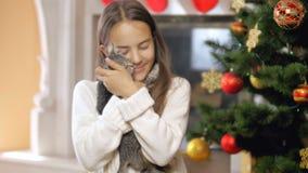 Retrato de la muchacha sonriente feliz en el suéter que juega con el gatito al lado del árbol de navidad adornado almacen de video