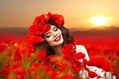 Retrato de la muchacha sonriente feliz hermosa que goza en la amapola roja f Fotos de archivo libres de regalías