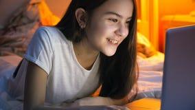 Retrato de la muchacha sonriente feliz que miente en cama y que tiene llamada video en el ordenador portátil en la noche Imagenes de archivo