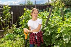 Retrato de la muchacha sonriente feliz que presenta en jardín con las verduras crecientes Imágenes de archivo libres de regalías