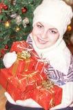 Retrato de la muchacha sonriente feliz que sostiene las cajas de regalo de la Navidad Imagen de archivo libre de regalías