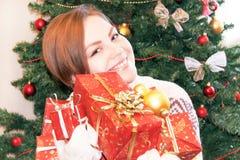 Retrato de la muchacha sonriente feliz que sostiene las cajas de regalo de la Navidad Fotos de archivo