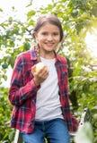 Retrato de la muchacha sonriente hermosa con el appler que presenta en jardín de la manzana Foto de archivo libre de regalías