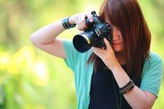 Retrato de la muchacha sonriente hermosa, con la cámara digital en sus manos Fotos de archivo libres de regalías