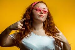 Retrato de la muchacha sonriente hermosa del pelirrojo que lleva los vidrios rosados grandes Fotos de archivo libres de regalías