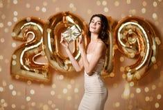 Retrato de la muchacha sonriente hermosa en confeti que lanza del vestido de oro brillante, divirtiéndose con oro 2018 globos en  imagen de archivo libre de regalías