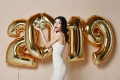 Retrato de la muchacha sonriente hermosa en confeti que lanza del vestido de oro brillante, divirtiéndose con oro 2019 globos en  fotos de archivo libres de regalías