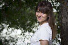 Retrato de la muchacha sonriente hermosa joven debajo del árbol grande en al aire libre Imagen de archivo libre de regalías