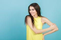 Retrato de la muchacha sonriente hermosa joven en camisa amarilla en fondo azul Imagen de archivo
