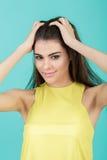 Retrato de la muchacha sonriente hermosa joven en camisa amarilla en fondo azul Fotografía de archivo