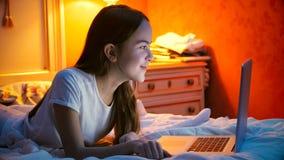 Retrato de la muchacha sonriente hermosa que miente en cama con el ordenador portátil antes de ir a dormir Foto de archivo